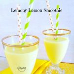 Lemon Smoothie in a crystal glass with orange and green straws. Glasses are sitting on a yellow napkin.