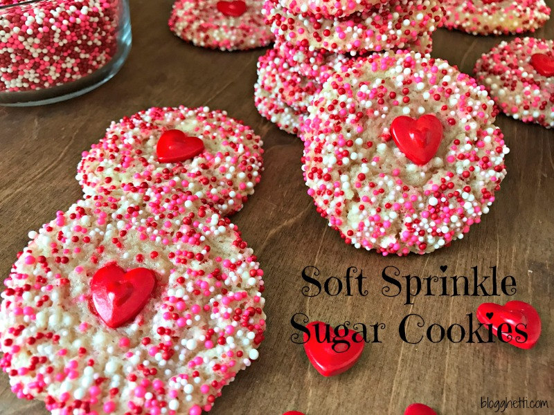 Surprise the Valentines in your life with these super Soft Sprinkle Sugar Cookies that are so easy to bake. No rolling or cutting out of the dough and super simple to decorate with the pink, red, and white sprinkles and a large red heart in the center of the cookie adds even more love to the baked goodness!
