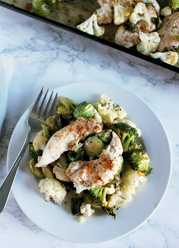 Chicken and vegetables on a white plate from a sheet pan meal