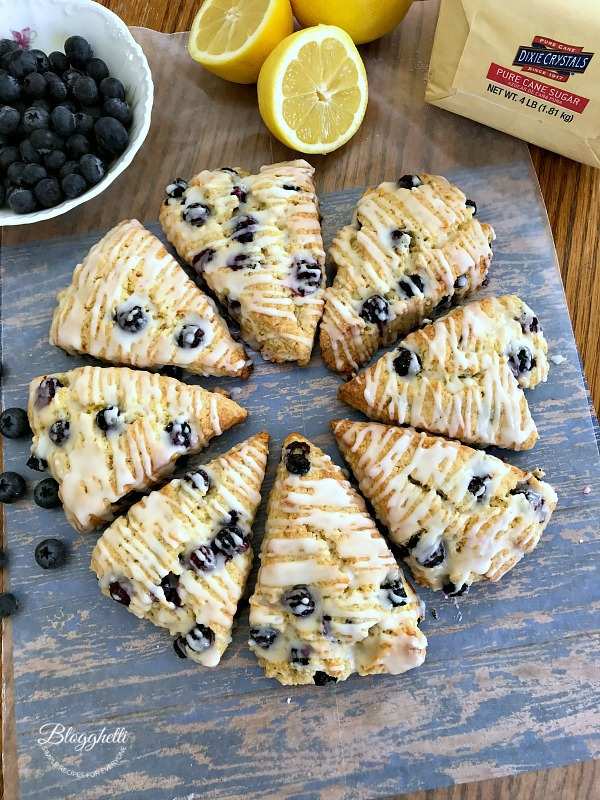 lemon blueberry scones pictured with a bowl of blueberries and a cut lemon