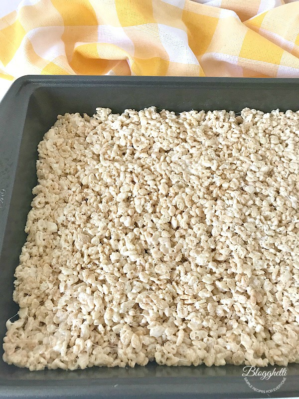 rice krispies treats pressed into pan to cool