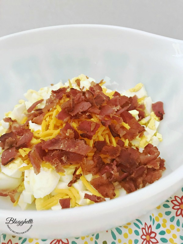 Bacon Cheddar Egg Salad in white bowl on top of a flowered towel