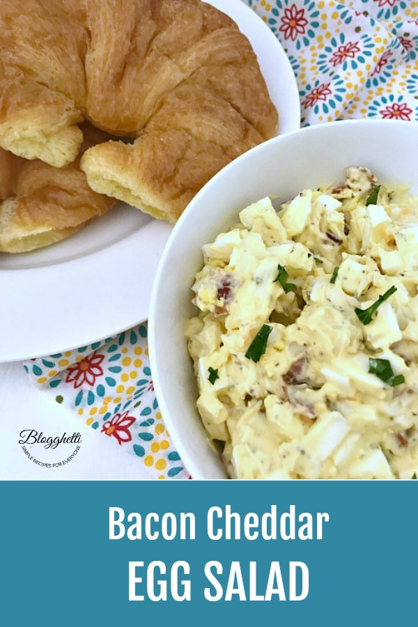 Bacon Cheddar Egg Salad in white bowl with a plate of crossiants beside it.
