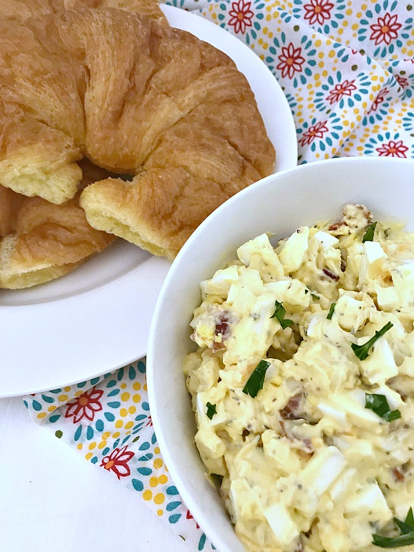 Bacon Cheddar Egg Salad in white bowl.. A plate of fresh crossiants are stacked beside the egg salad