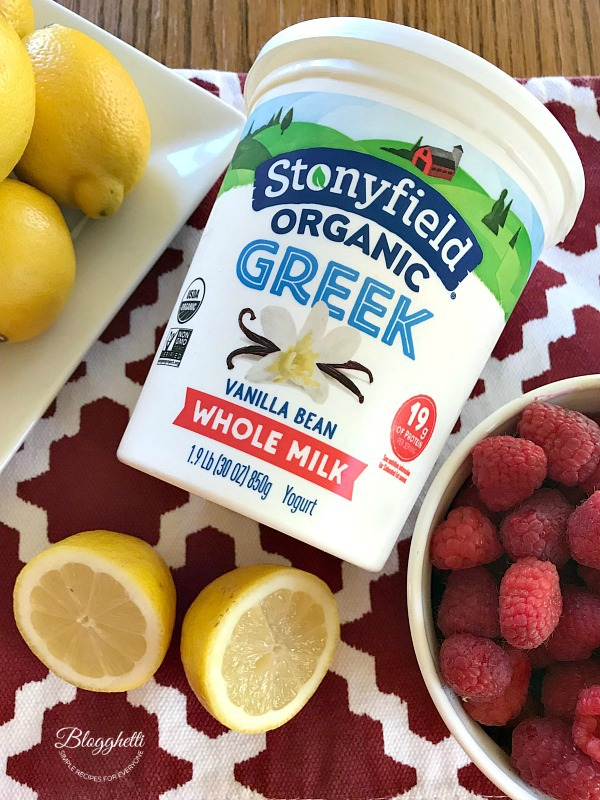 Stonyfield Greek Yogurt with a plate of lemons and a bowl of raspberries