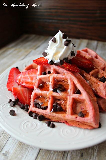 Strawberry Milkshake Waffles with fresh strawberries, chocolate chips, and whipped cream on top.