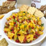Bowl of homemade peach salsa with cornbread crisps to dip