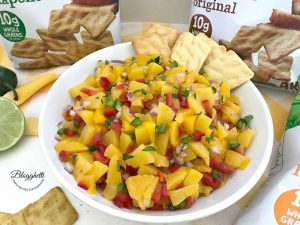 Bowl of homemade peach salsa with cornbread crisps to dip