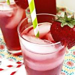 close up of Sparkling Hibiscus Iced Tea in glasses garnished with straws and strawberries. #hibiscus #icedtea #tea #drinks